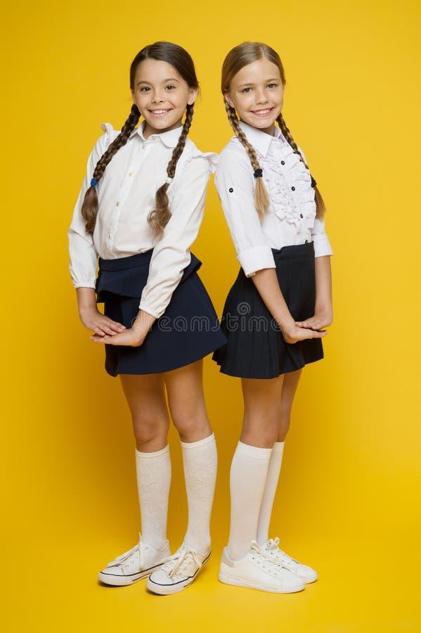 Beste Schüler sprechen zu Alles nach rechts machen Ausgezeichnete Schüler Perfekte einheitliche Ausstattung der Mädchen auf gelbe lizenzfreie stockfotos