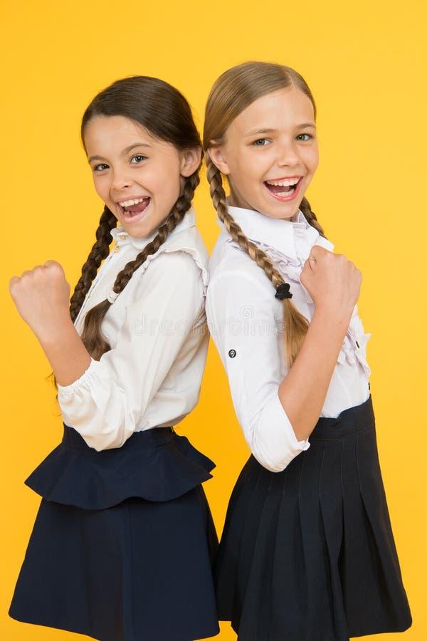 Beste Schüler sprechen zu Ausgezeichnete Schüler Perfekte einheitliche Ausstattung der Mädchen auf gelbem Hintergrund Alles nach  lizenzfreie stockfotos