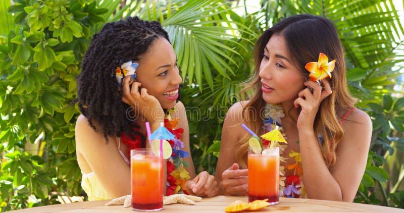 Beste vrienden die op vakantie aan overzeese shells en het drinken cocktails luisteren royalty-vrije stock foto