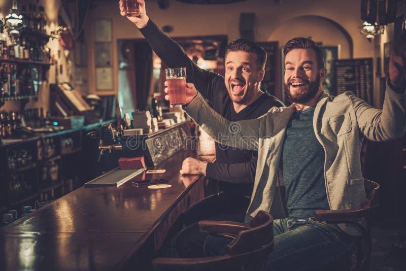 Beste vrienden die pret hebben die op een voetbalspel op TV letten en ontwerpbier drinken bij barteller in bar stock fotografie
