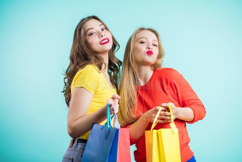 Beste vrienden die pret hebben, die op blauwe achtergrond lachen Dragend kleren en met een glimlach bekijk de camera stock fotografie