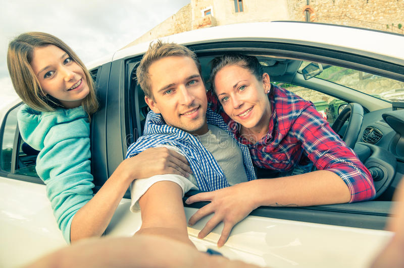 Beste vrienden die pret hebben samen bij autoreis op de weg stock afbeeldingen