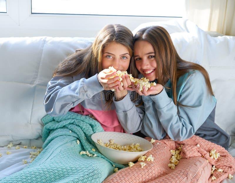 Beste vriendenmeisjes bij bank die pret met popcorn hebben stock foto's
