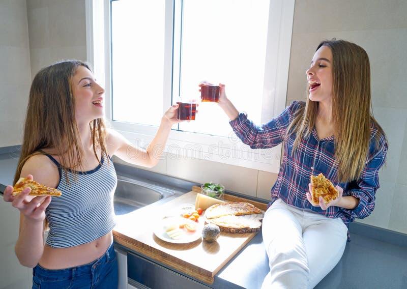 Beste vriendenmeisjes die pizza in de keuken eten royalty-vrije stock foto's