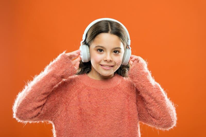 Beste vrije muziek apps voor uw mobiel apparaat Geniet van geluid Slijtagehoofdtelefoons van het meisjes luisteren de leuke weini stock foto's