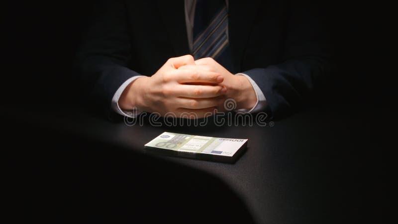 Bestechungsgeld: Geld zwischen zwei Geschäftsmännern auf einer Tabelle am Verhandlungszeiteuro stockfoto