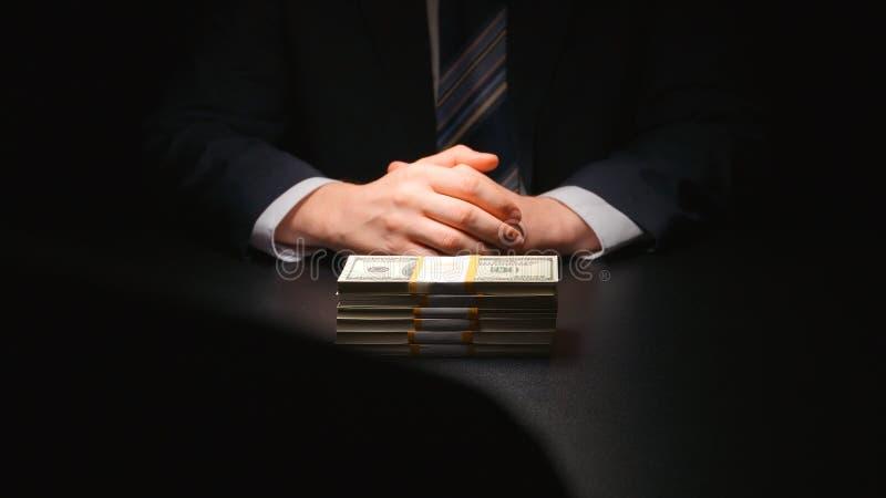 BESTECHUNGSGELD: Geldbündellüge zwischen zwei Geschäftsmännern lizenzfreie stockfotografie