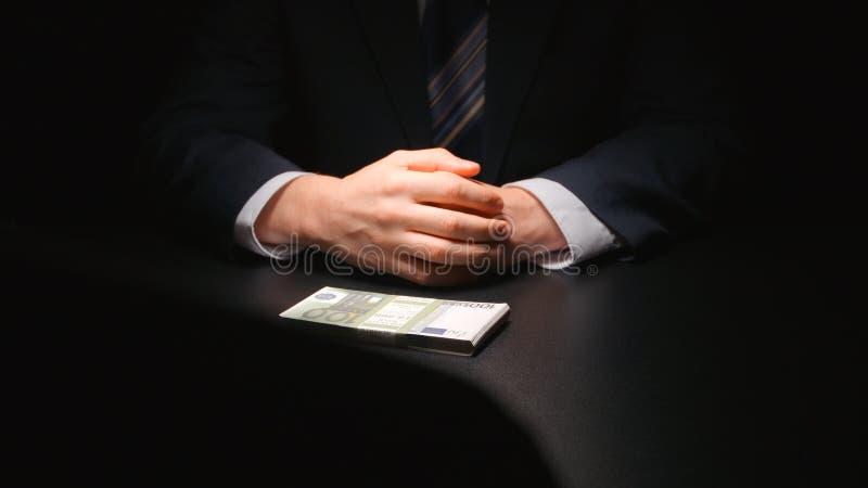 BESTECHUNGSGELD: Geschäftsmann wartet und steckt ein Geld auf einen Tabelle EURO - Zweipersonen stockbilder