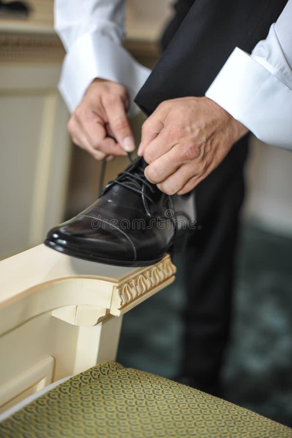 Bester Mann, der zu einem speziellen Tag fertig wird Ein Bräutigam, der auf Schuhe sich setzt, wie er in der formellen Kleidung a lizenzfreie stockfotos