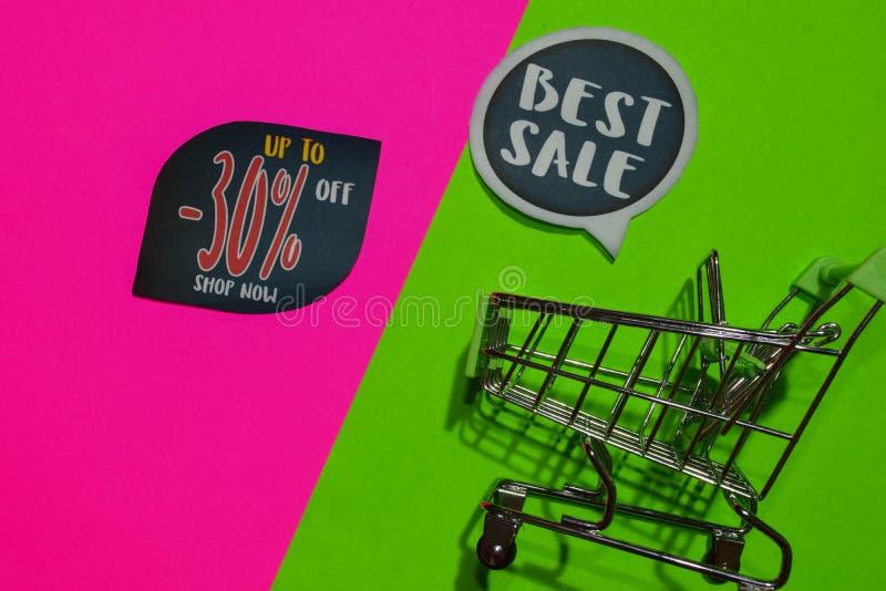 Bester Verkauf und bis -30% weg vom Geschäfts-jetzt Text und dem Einkaufswagen stockfoto