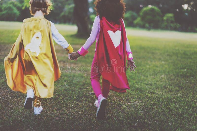 Bestfriends Superherosmå flickor som går begrepp arkivfoto