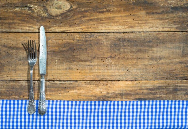Bestick med den blåa och vita tabelltorkduken på lantligt trä med kopieringsutrymme för menykort arkivbild