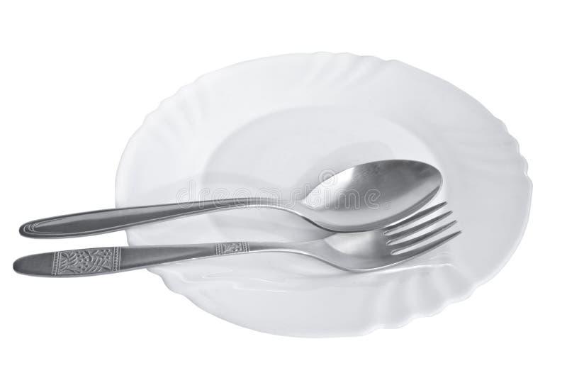 Bestick - sked och gaffel på den vita porslinplattan som isoleras på vit bakgrund royaltyfria bilder