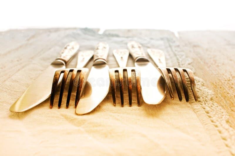 Bestickgafflar, knivar på en retro stil för lantlig trätabell, närbild som tonas arkivfoton