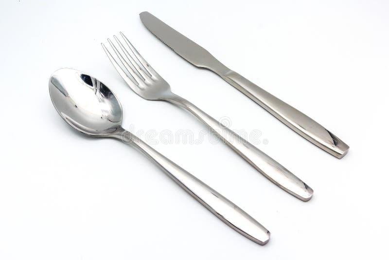 Bestickuppsättning med gaffeln, kniven och skeden som isoleras på vit bakgrund arkivfoto