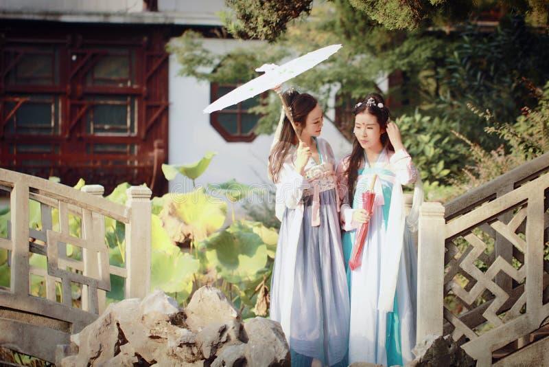 Bestie próximo das amigas no traje antigo tradicional chinês em um jardim imagens de stock royalty free