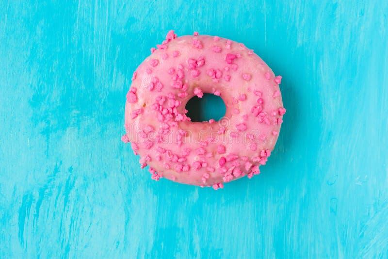 Bestrooit de roze verglaasde doughnut met suiker op lichtblauwe achtergrond, in het midden, copyspace, malplaatje, verjaardag, ka royalty-vrije stock afbeelding