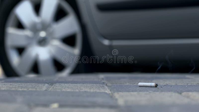 Bestuurder die stomp van sigaret van autoraam op bestrating, vuile stoep werpen stock foto's