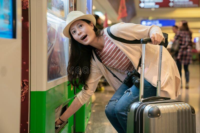 Besucher, der Sachen vom Automaten nimmt lizenzfreie stockbilder