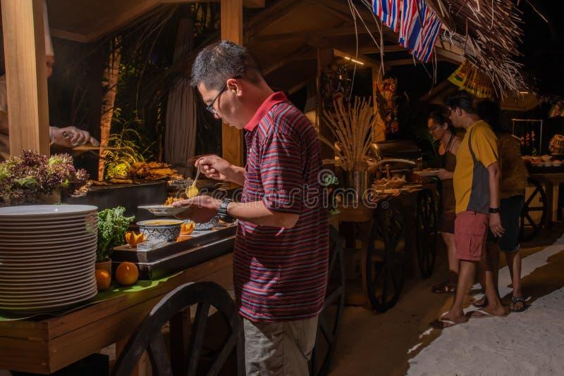 Besucher, die Nahrung während des internationalen Kücheabendessens draußen gegründet am Inselrestaurant nehmen lizenzfreie stockfotografie