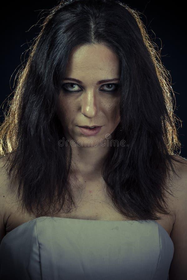 Besvära, den ledsna brunettkvinnan med långt hår och aftonkappan royaltyfria bilder