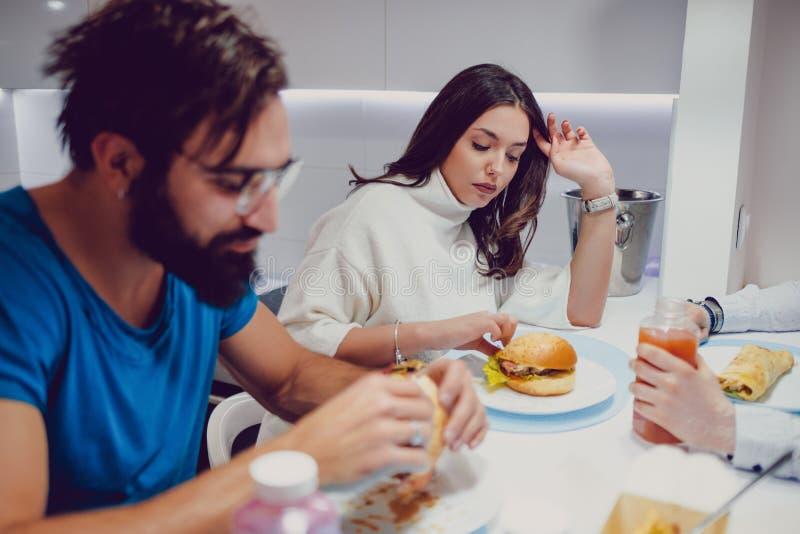 Besvärade par som äter matställen med vänner royaltyfri foto