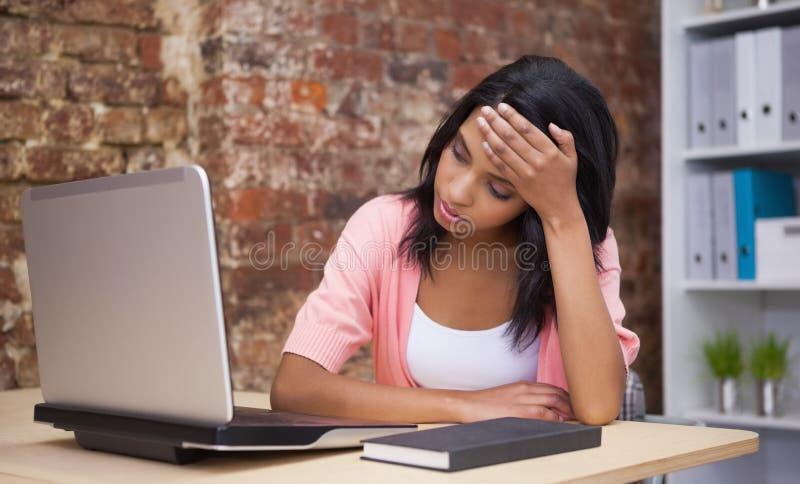 Besvärat kvinnasammanträde på hans skrivbord med en bärbar dator royaltyfri foto