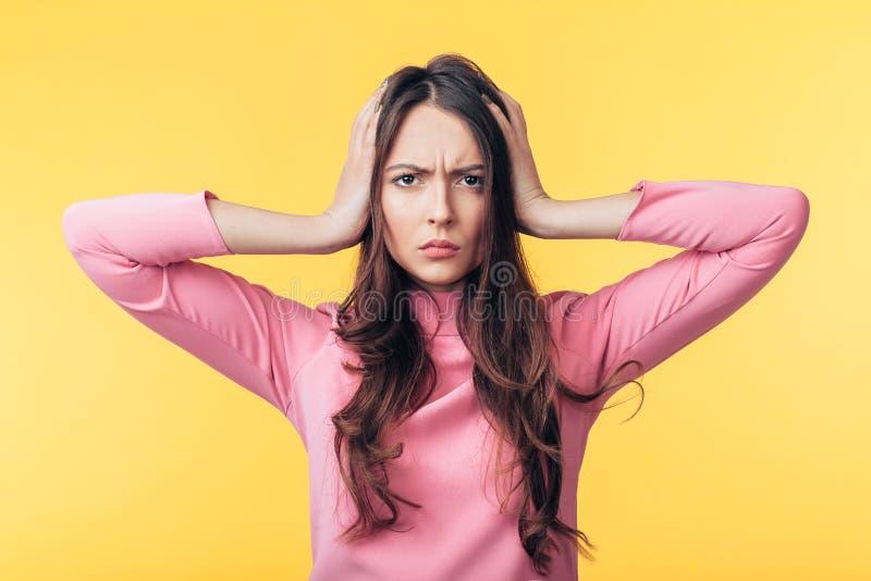 Besvikelse belastade kvinnan med huvudvärk som isolerades på gul bakgrund arkivbild