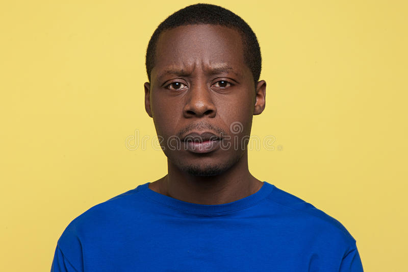 Besvikelseuttryck Olycklig svart man arkivfoto