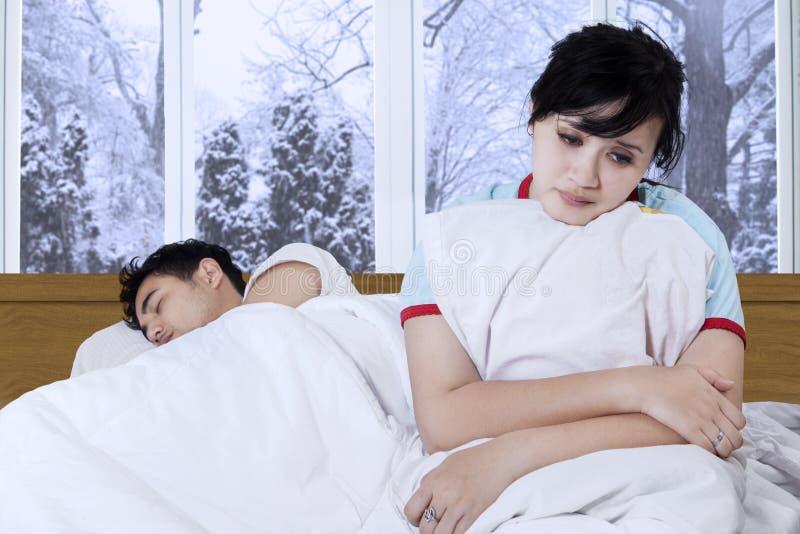 Besviken flicka på säng fotografering för bildbyråer