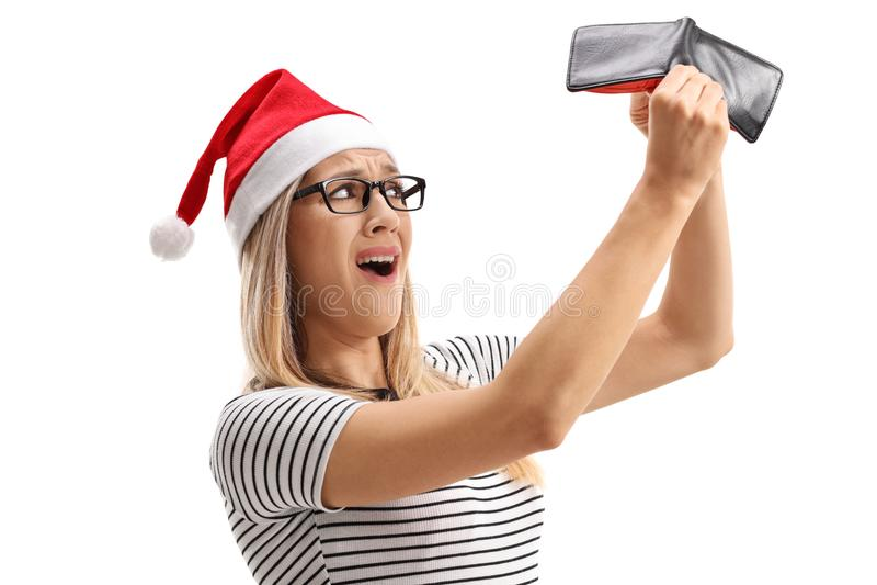 Besviken kvinna med en julhatt som rymmer en tom plånbok royaltyfri bild