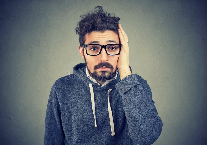 Besviken stressad skäggig ung man arkivfoto