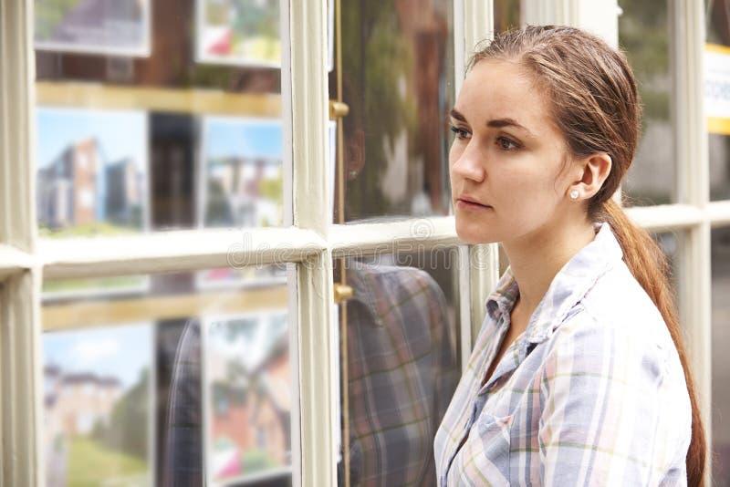 Besviken ung kvinna som ser i fönster av fastighetsmäklare arkivfoton