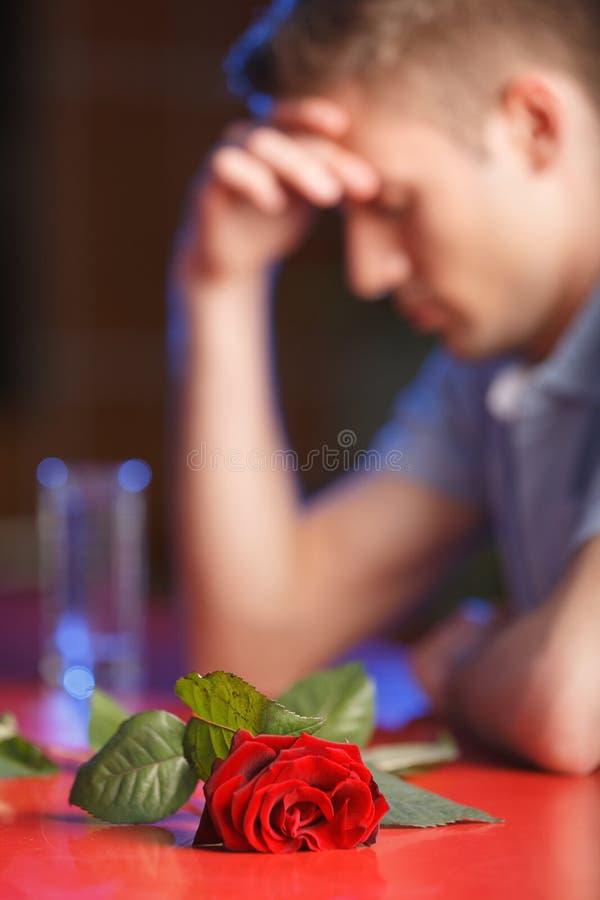 Besviket mansammanträde med den röda rosen på tabellen royaltyfri bild