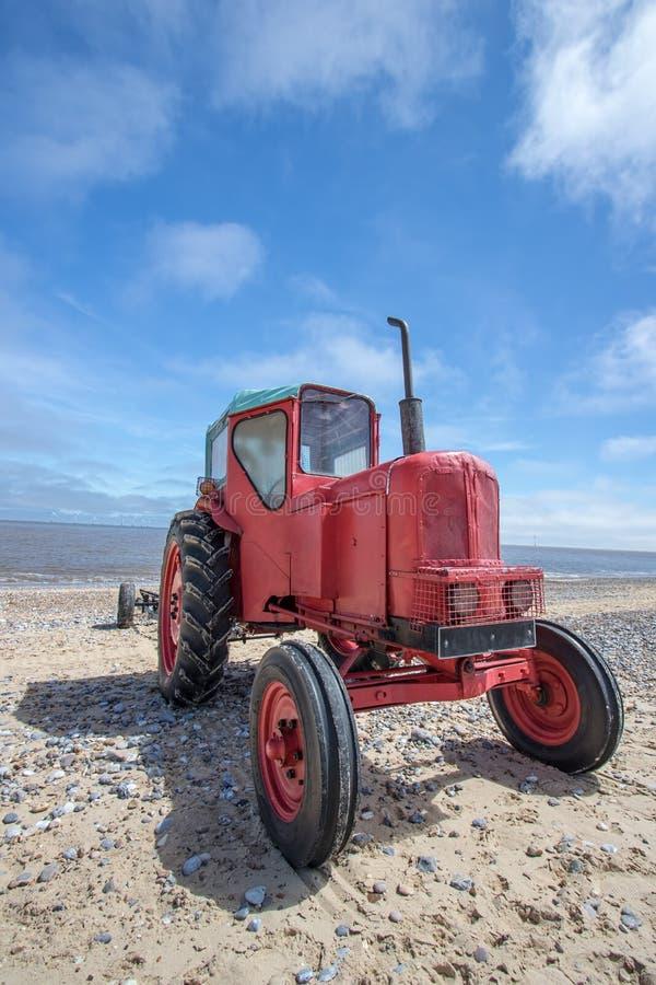 Besynnerlig röd diesel- strandtraktor Liten röd traktor för tappning arkivfoton