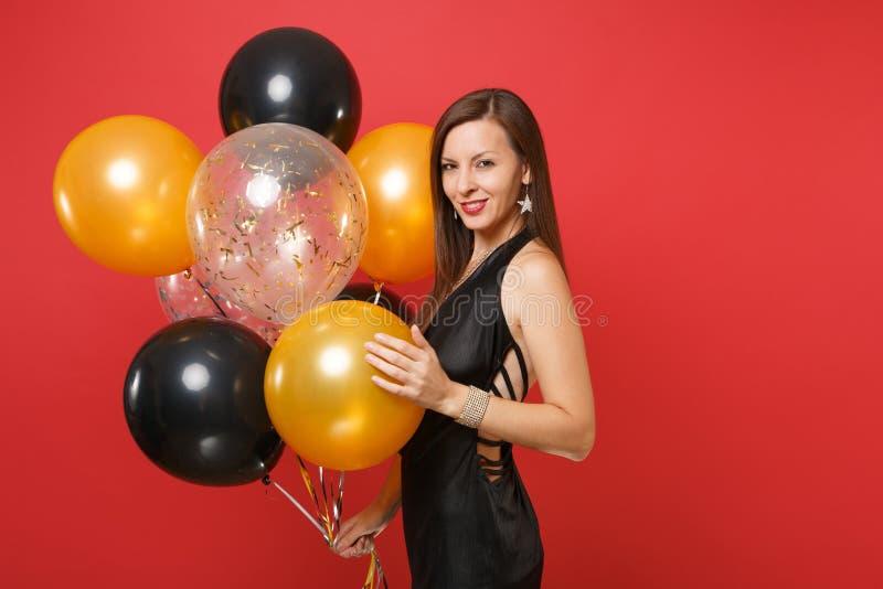 Betäubendes junges Mädchen in der kleinen Schwarze feiernd, Luftballone halten lokalisiert auf rotem Hintergrund St.-Valentinsgru stockbilder