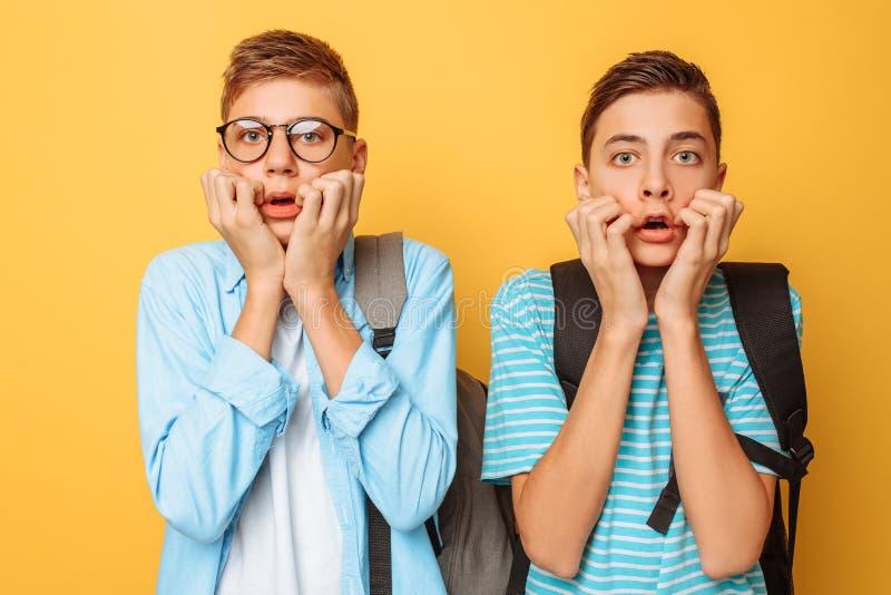 Betäubt, entsetzt, erdrosseln zwei Kerle, Jugendliche mit Furcht, bedecken ihre Münder mit beiden Händen, auf einem gelben Hinter stockbild