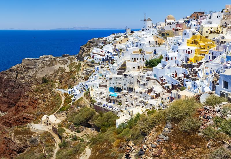 Betäubungs, erstaunliche und schöne klassische griechische Architektur des Weiß und der Karamellfarbe mit unglaublichen Windmühle lizenzfreies stockbild