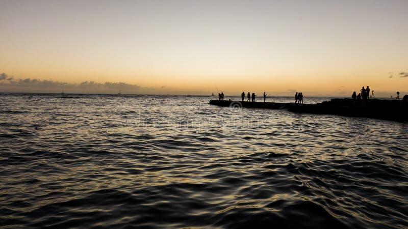 Betäubungsluftbrummenansicht kurz nach dem Sonnenuntergang, der einen Pier/eine Anlegestelle an Waikiki-Strand zeigt Touristen un lizenzfreie stockfotos