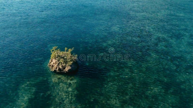 Betäubungsluftbrummenbild eines bunten Meeresgrundriffs mit einem Klippenfelsen, der aus Wasser in den flachen Meeren des ruhigen stockfoto