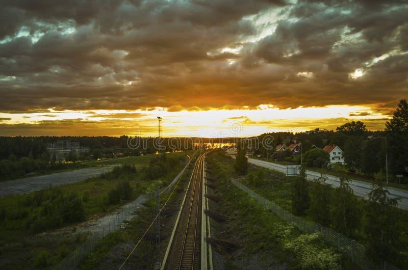 Betäubungsreflexion des Sonnenlichts auf beweglicher Wolke und der führenden Zuglinie zum orange Horizont am schönen Sommertag in lizenzfreie stockfotografie