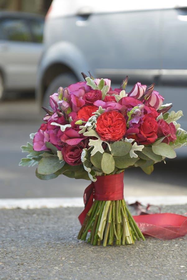 Betäubungsroter Brautblumenstrauß Die Braut mit einer Blume lizenzfreies stockfoto