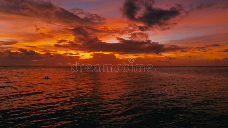 Betäubungsschönes Luftbrummenbild eines roten tropischen Sonnenuntergangs über dem Seeozean mit Zwei-mann in einem Kanufischen lizenzfreies stockfoto