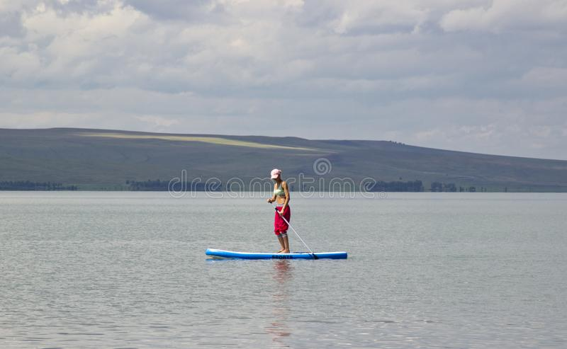 Betäubungsschattenbild eines schönen Mädchens, das an auf das Surfbrett schwimmt stockfoto