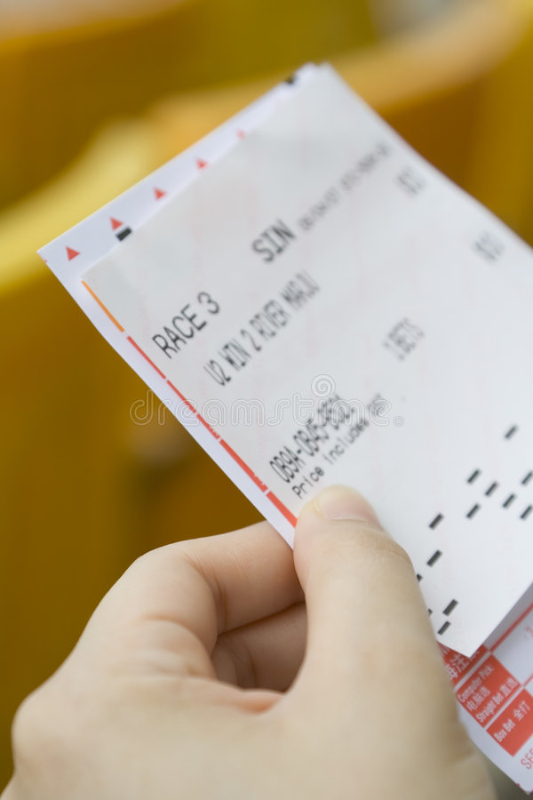 Bet slip for horse racing. Hand holding a bet slip for horse racing stock images