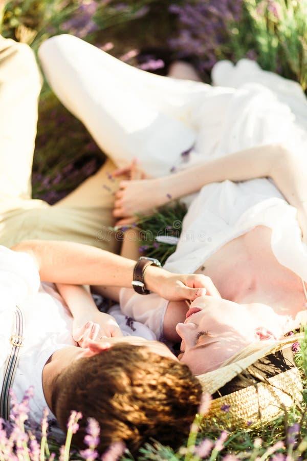 Bet?ubungsportr?t der Braut und des Br?utigams, die auf einem Lavendelgebiet liegen stockbild