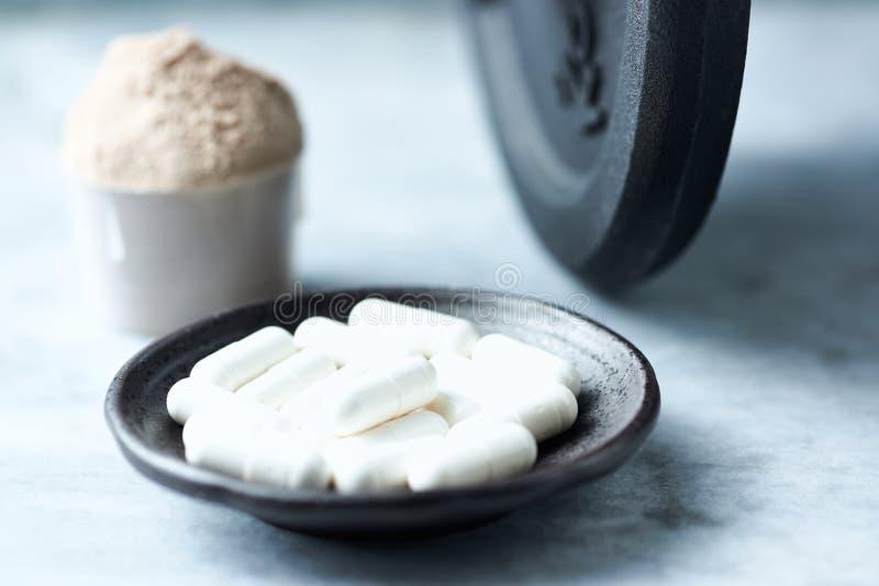 Beta胺基代丙酸乳清蛋白胶囊、瓢和一个哑铃在背景中 体育营养 图库摄影