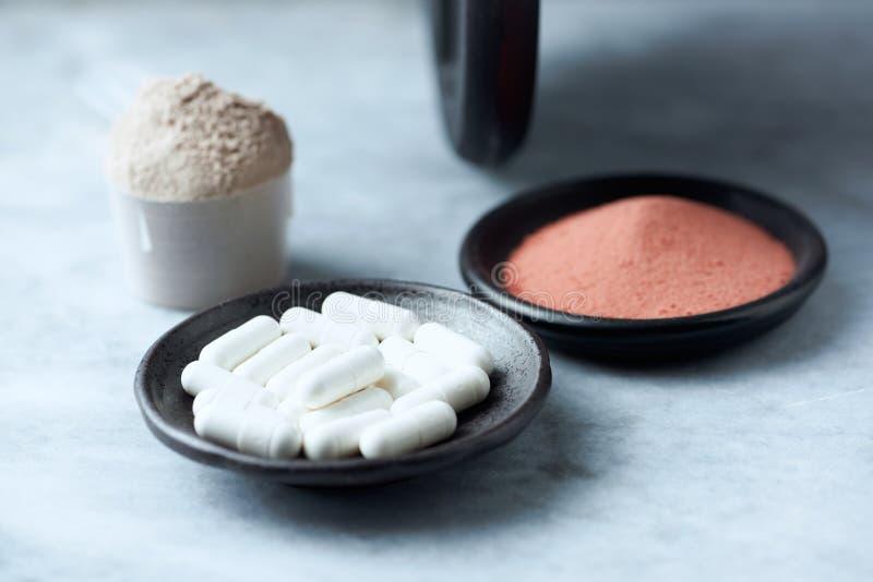 Beta胺基代丙酸乳清蛋白胶囊、瓢,肌酸粉末和一个哑铃在背景中 库存图片