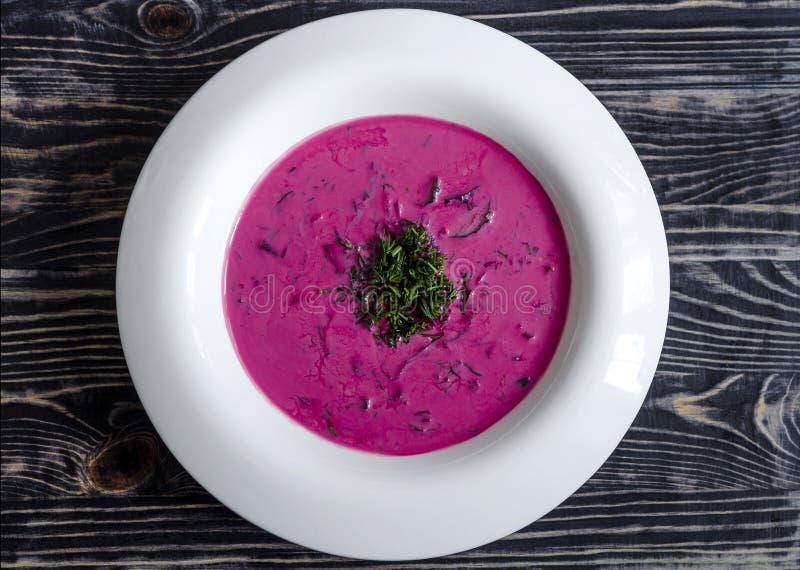 Beta-grönsak soppa med gräsplaner på en mörk träbakgrund för vit platta royaltyfri fotografi