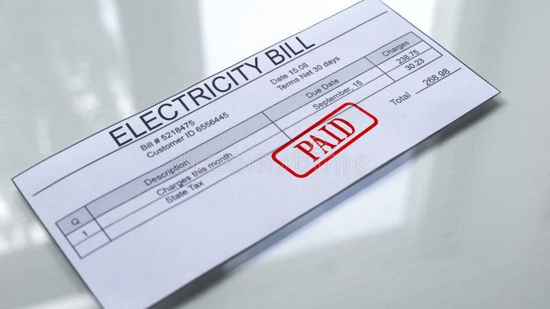Betaalde verbinding die op elektriciteitsrekening wordt gestempeld, betaling voor de diensten, maanduitgaven stock fotografie